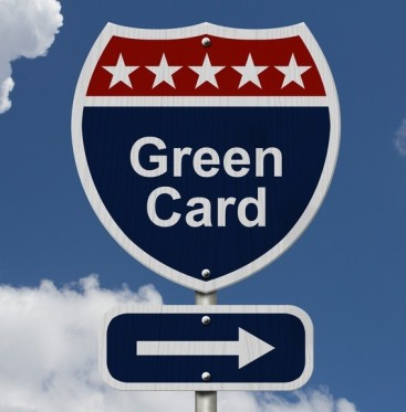 Green Card this way, Blue, Red and White highway sign with words Green Card with sky background
